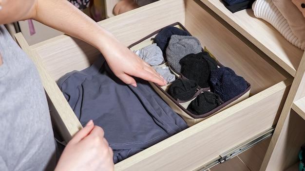 Mulher escolhe meias na gaveta de um grande armário na sala