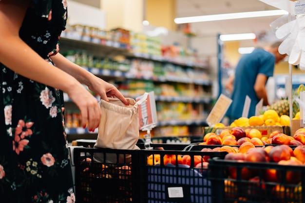 Mulher escolhe mercado de alimentos de frutas e legumes