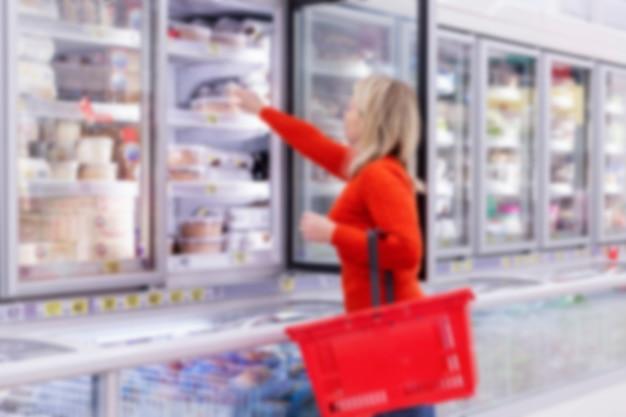 Mulher escolhe produtos no departamento de congelamento em um supermercado. alimentação saudável e estilo de vida. vista lateral. borrado.