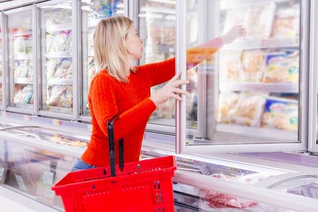 Mulher escolhe produtos no departamento de congelamento em um supermercado. alimentação saudável e estilo de vida. vista lateral.