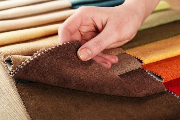 Mulher escolhe retalhos de tecido colorido na mesa de perto