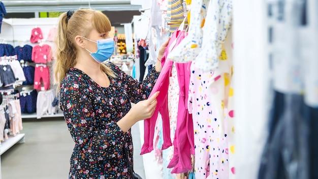 Mulher escolhe roupas de bebê na loja. foco seletivo. comprar.