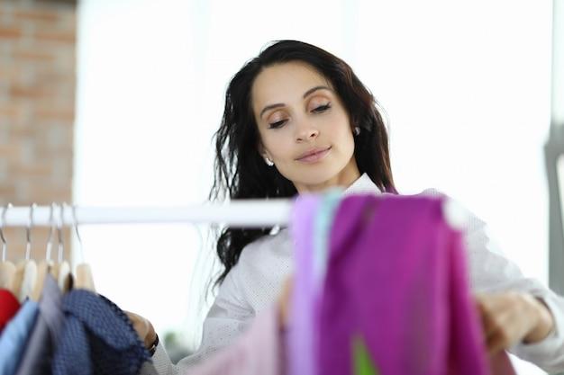 Mulher escolhe roupas no cabide.