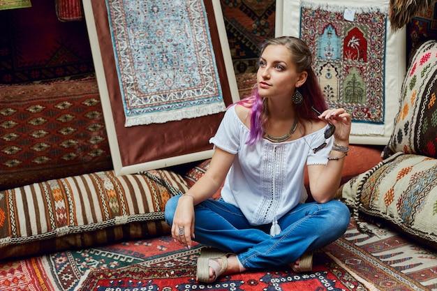 Mulher escolhe tapete no mercado.