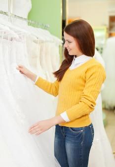 Mulher escolhe vestido na loja de moda de casamento