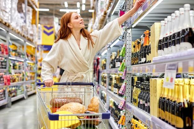 Mulher escolhendo álcool na loja, carrinho pegando uma garrafa de vinho da prateleira, retrato de mulher em roupão de banho no corredor