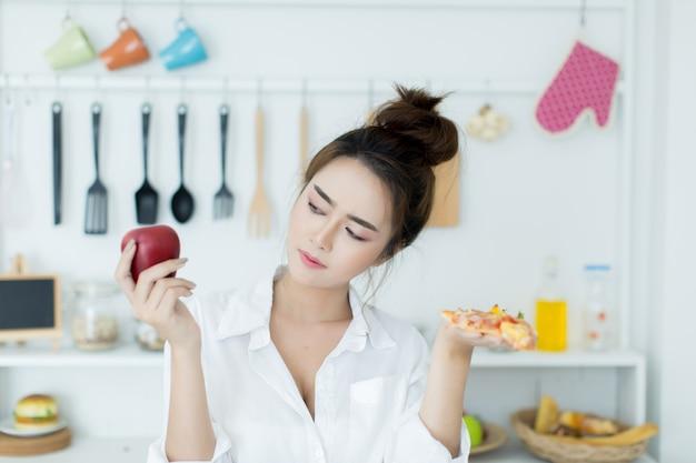 Mulher escolhendo entre apple e pizza