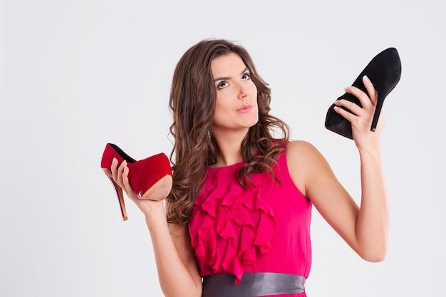 Mulher escolhendo entre salto alto vermelho e preto