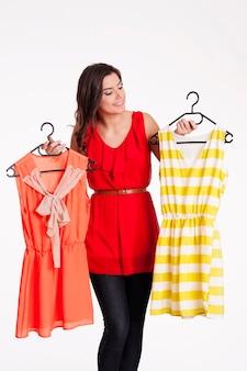 Mulher escolhendo entre vestido laranja e listrado