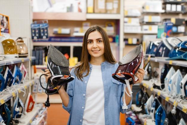 Mulher escolhendo ferro elétrico na loja de eletrônicos. mulher comprando eletrodomésticos no mercado