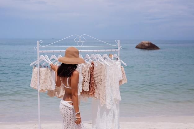 Mulher escolhendo roupas de malha em cabides na praia