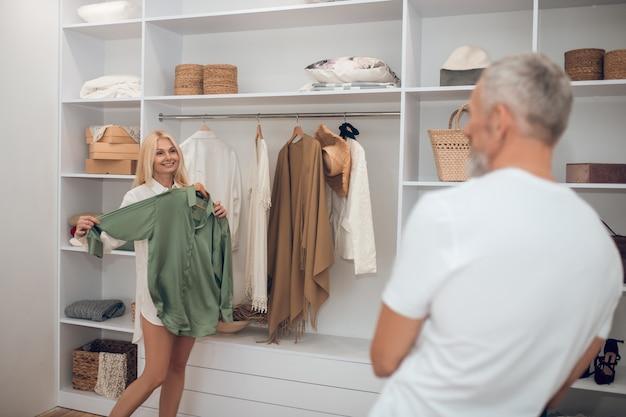 Mulher escolhendo roupas em um guarda-roupa e mostrando ao marido