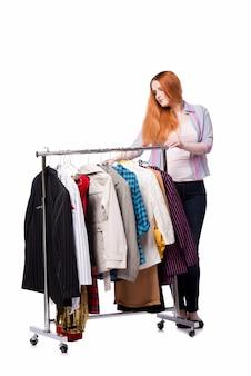 Mulher escolhendo roupas na loja isolada no branco