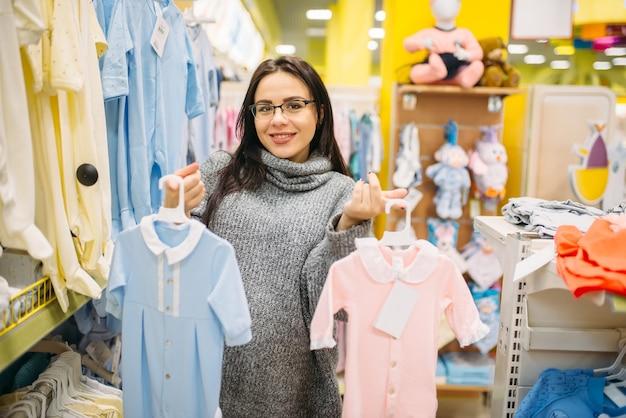 Mulher escolhendo roupas na loja para recém-nascidos. futura mãe em loja de produtos para bebês