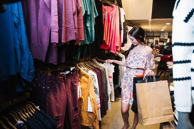 Mulher escolhendo roupas na loja
