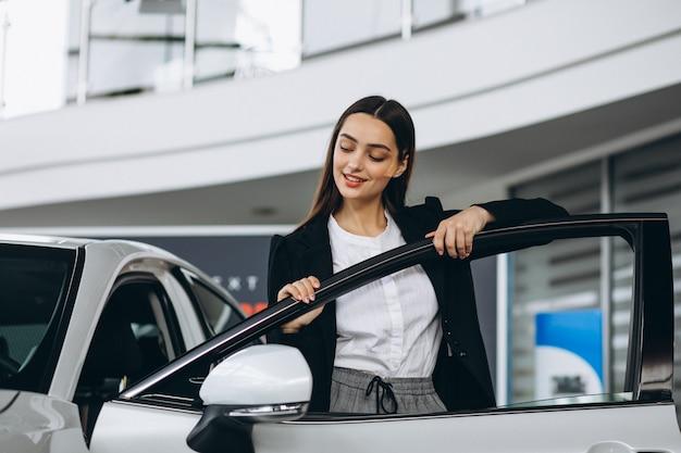 Mulher escolhendo um carro em uma sala de exposições