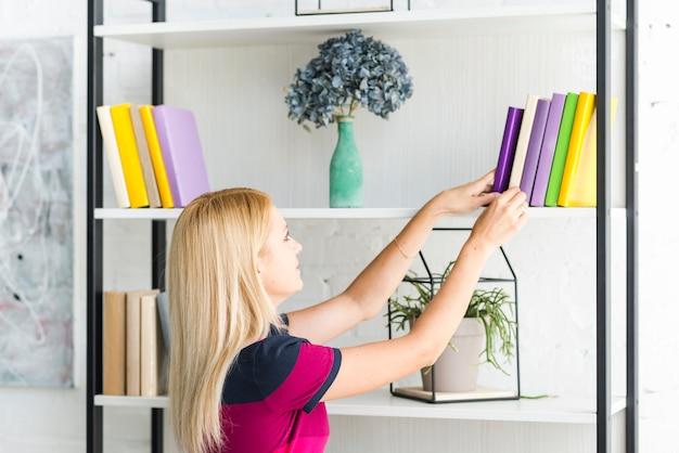Mulher escolhendo um livro da prateleira em casa