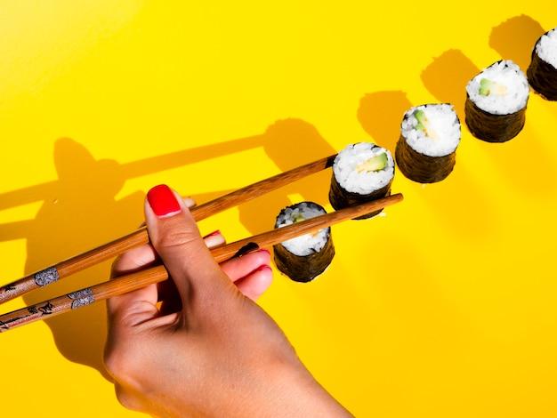 Mulher escolhendo um rolo nigiri de uma mesa amarela