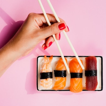 Mulher escolhendo um sushi do prato