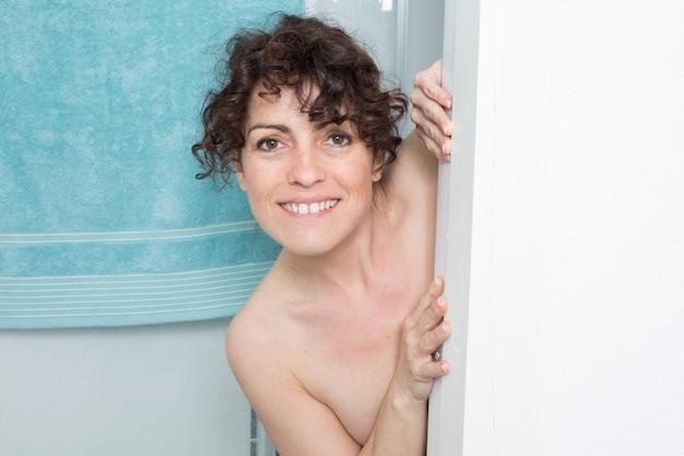 Mulher escondida atrás de uma parede do banheiro