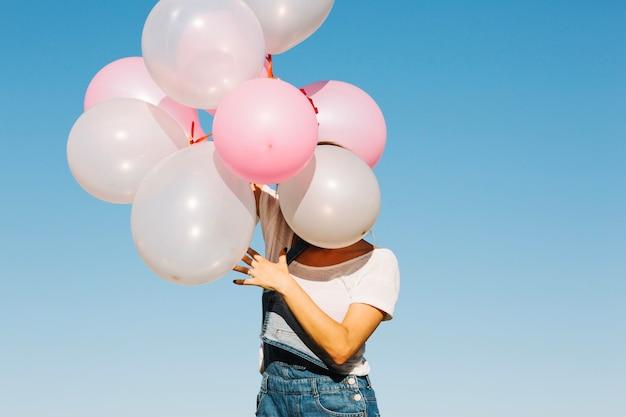 Mulher escondida face atrás de balões Foto gratuita