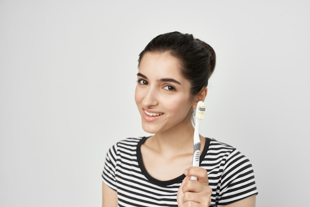 Mulher escova os dentes com uma escova de dentes isolada no fundo