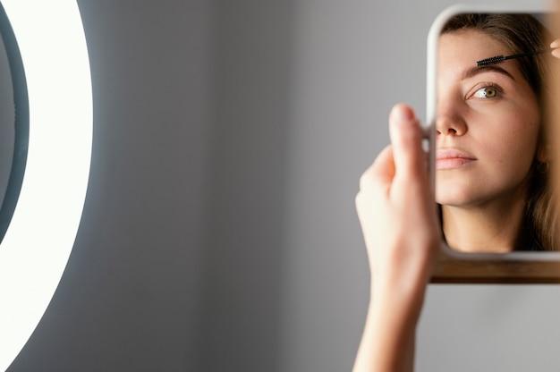 Mulher escovando as sobrancelhas enquanto se olha no espelho após tratamento com espaço de cópia