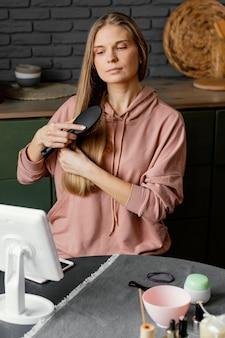 Mulher escovando cabelo com dose média