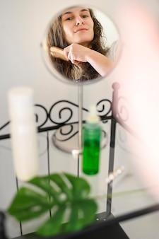 Mulher escovando enquanto olha no espelho