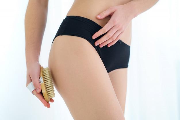 Mulher escovando nádegas da pele e bunda com uma escova de madeira seca para prevenir e tratar o problema de celulite e corpo após o banho em casa. saúde da pele