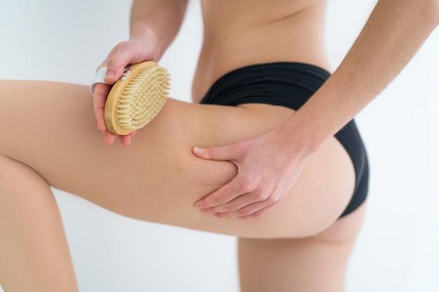 Mulher escovando nádegas da pele e bunda com uma escova de madeira seca para prevenir e tratar o problema de celulite e corpo após o banho no banheiro em casa. saúde da pele