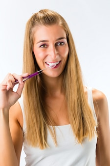 Mulher escovando os dentes com uma escova de dentes