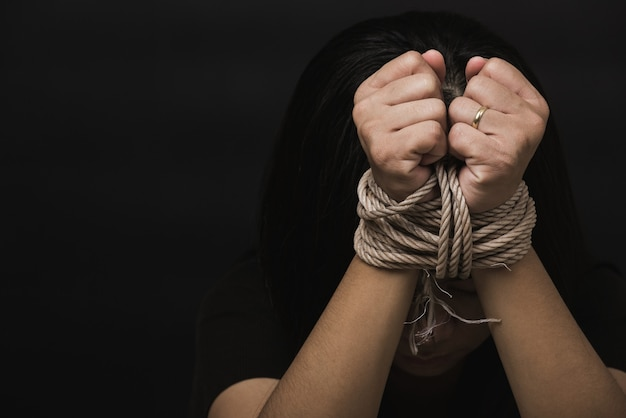 Mulher escrava teme ter as mãos amarradas com corda