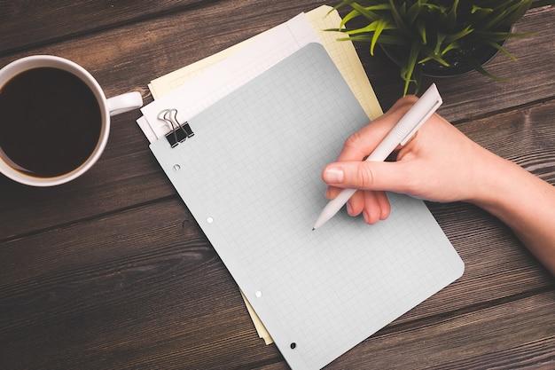 Mulher escreve algo em uma folha de papel em uma mesa de madeira