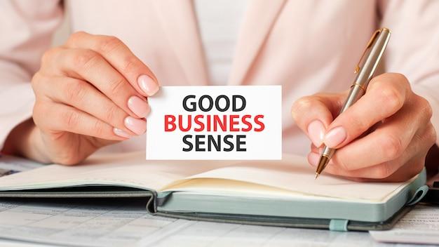 Mulher escreve em um caderno com uma caneta de prata e um cartão de preensão de mão com o texto: bom senso para os negócios. fundo rosa, vista frontal. conceito de negócios e educação.