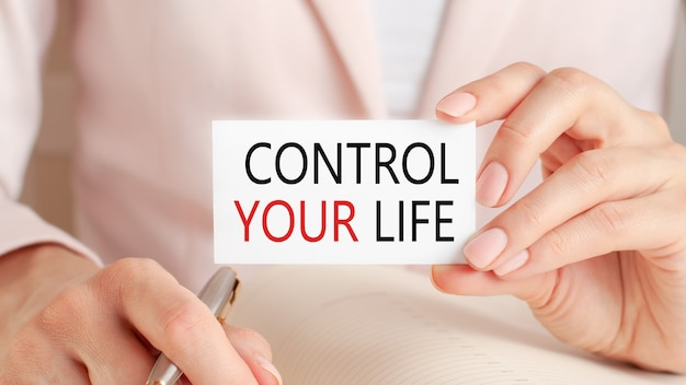 Mulher escreve em um caderno com uma caneta de prata e um cartão de preensão de mão com o texto: controle sua vida.