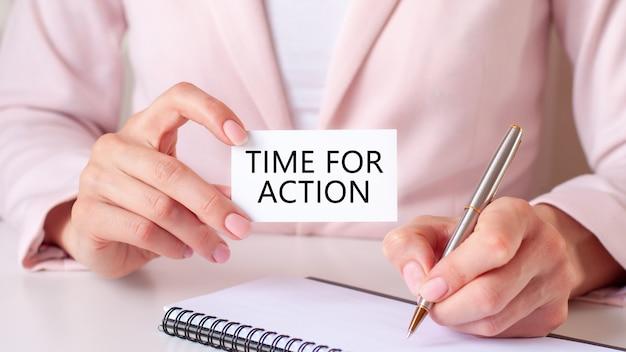 Mulher escreve em um caderno com uma caneta prateada e um cartão de mão com o texto: hora de ação. conceito de negócios e educação.