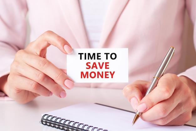 Mulher escreve em um caderno com uma caneta prateada e uma mão segurando um cartão com o texto: hora de economizar dinheiro