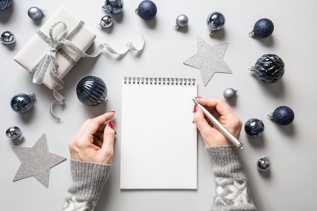Mulher escreve metas, lista de verificação, planos e sonhos para o ano novo.