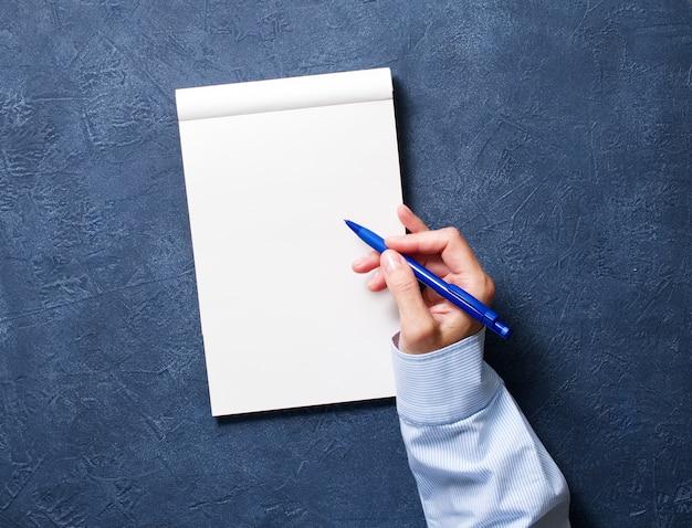 Mulher escreve no caderno na mesa azul escuro, mão na camisa, segurando um lápis, caderno de desenho