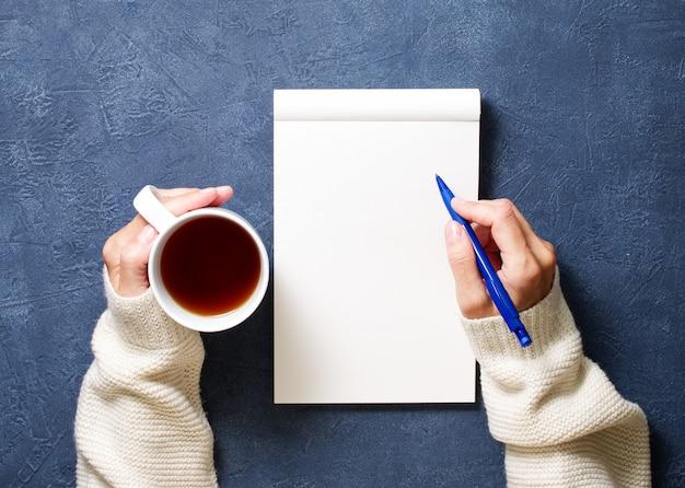 Mulher escreve no caderno na mesa azul escuro, mão na camisa, segurando um lápis, xícara de chá