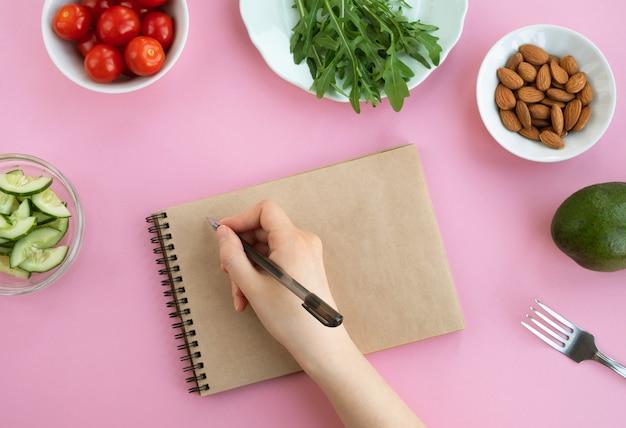 Mulher escreve plano de dieta em um notebook