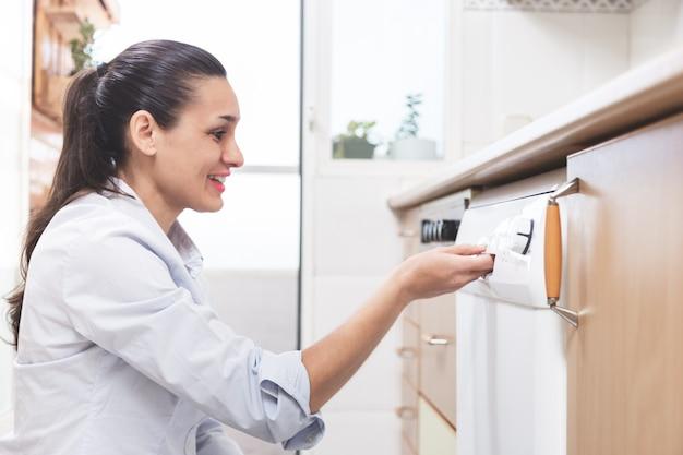 Mulher, escrevendo a máquina de lavar louça na cozinha do apartamento dela. conceito de trabalho doméstico.