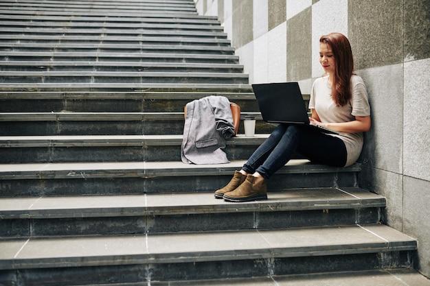 Mulher escrevendo artigo no laptop