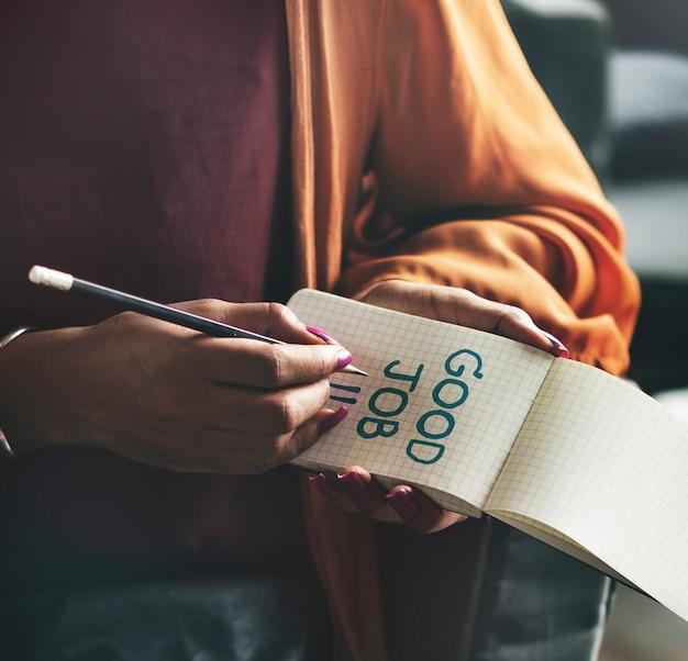 Mulher escrevendo bom trabalho em um bloco de notas