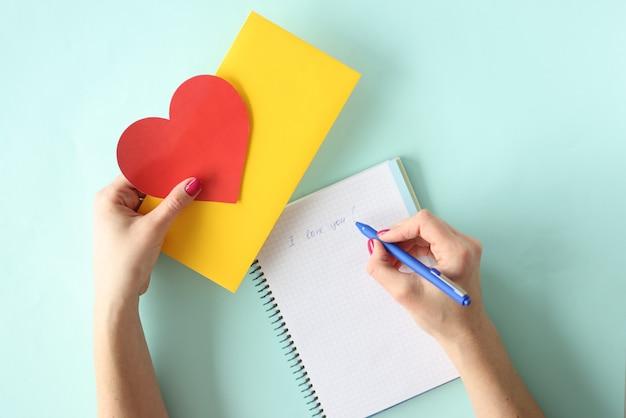 Mulher escrevendo carta com caneta esferográfica para dia dos namorados closeup