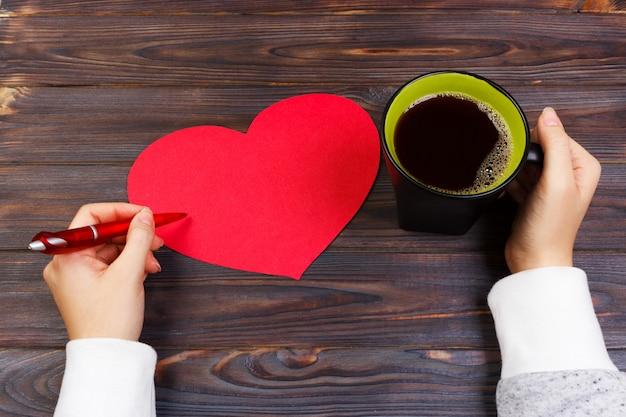 Mulher escrevendo carta de amor e bebendo café preto