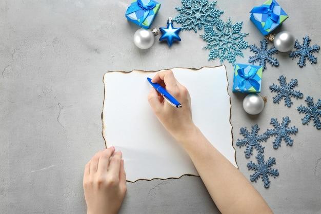 Mulher escrevendo carta para o papai noel à mesa