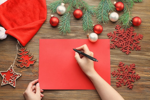 Mulher escrevendo carta para o papai noel em uma mesa de madeira