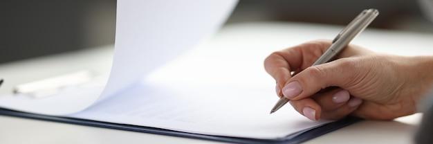 Mulher escrevendo com caneta esferográfica em documentos na área de transferência na estratégia de negócios do escritório closeup